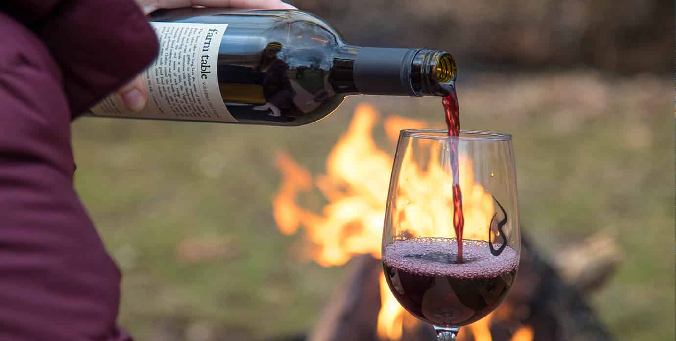 Pouring red wine into a glass in front of a fire