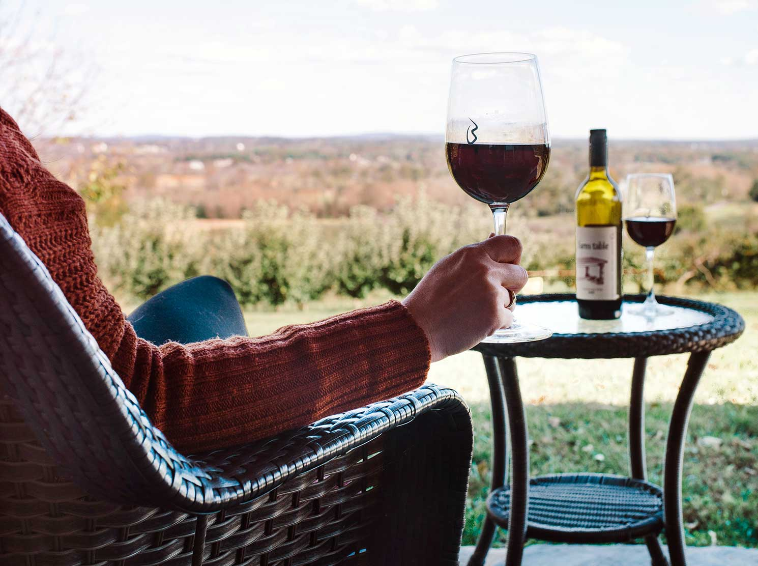 Woman enjoying glass of red wine on patio