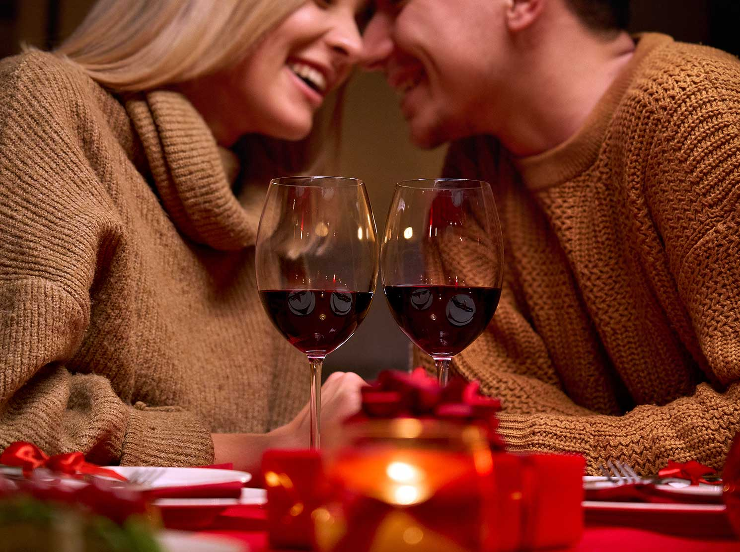 Couple enjoying red wine in candle light