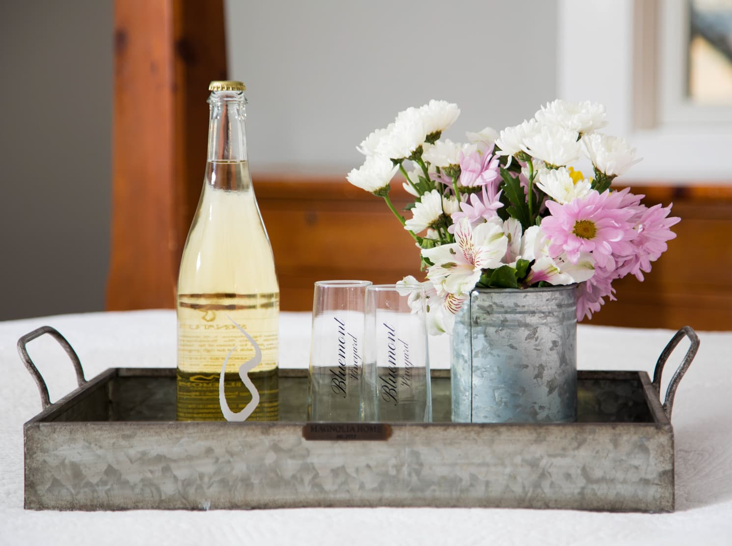 Bluemont Vineyard sparkling wine with two flutes and a bouquet of flowers