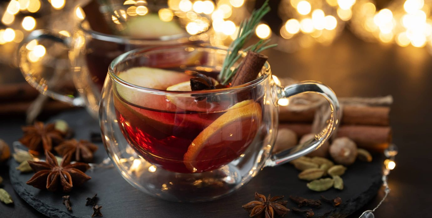Christmas lights and mulled wine with cinnamon, orange, and star anise